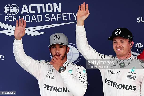 Mercedes AMG Petronas F1 Team's German driver Nico Rosberg celebrates taking pole position next to his teammate Mercedes AMG Petronas F1 Team's...