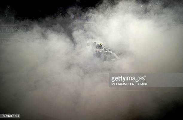 TOPSHOT Mercedes AMG Petronas F1 Team's German driver Nico Rosberg celebrates at the end of the Abu Dhabi Formula One Grand Prix at the Yas Marina...