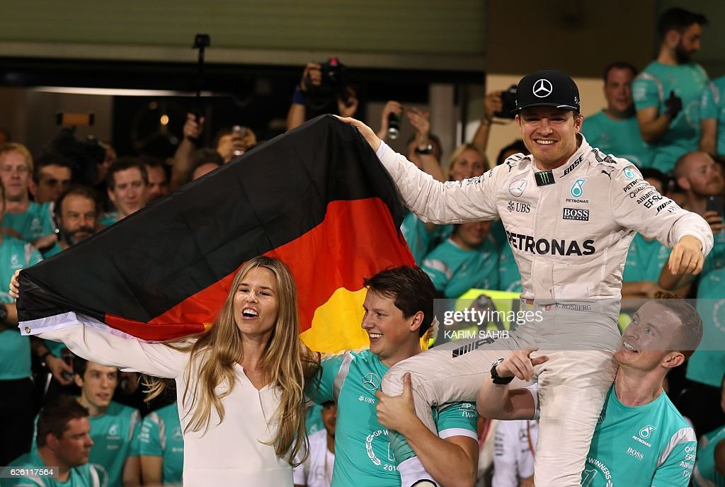 Mercedes AMG Petronas F1 Team's German driver Nico Rosberg (R) celebrates with his wife Vivian Sibold at the end of the Abu Dhabi Formula One Grand Prix at the Yas Marina circuit on November 27, 2016. Nico Rosberg won his maiden Formula One world title by securing second place behind his Mercedes arch-rival Lewis Hamilton in the Abu Dhabi Grand Prix. / AFP / KARIM