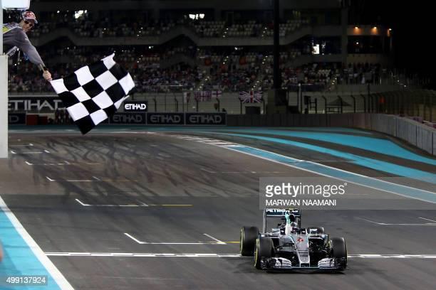 Mercedes AMG Petronas F1 Team's German driver Nico Rosberg crosses the finish line to win at the Yas Marina circuit in Abu Dhabi on November 29 2015...