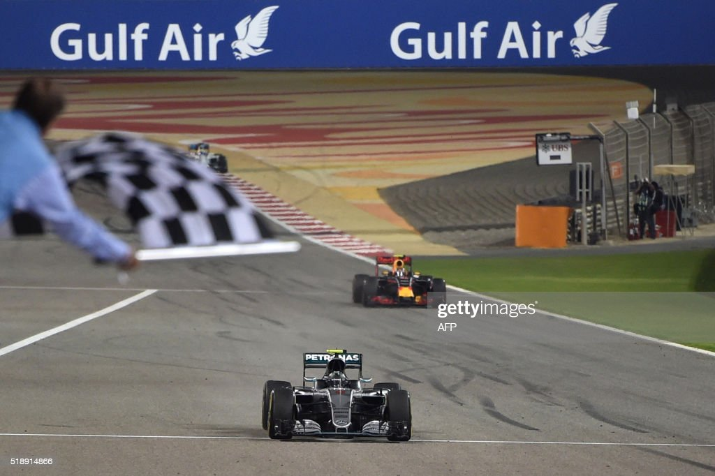 TOPSHOT - Mercedes AMG Petronas F1 Team's German driver Nico Rosberg crosses the finish line ahead of Ferrari's Finnish driver Kimi Raikkonen and Mercedes AMG Petronas F1 Team's British driver Lewis Hamilton during the Formula One Bahrain Grand Prix at the Sakhir circuit in the desert south of the Bahraini capital, Manama, on April 3, 2016.