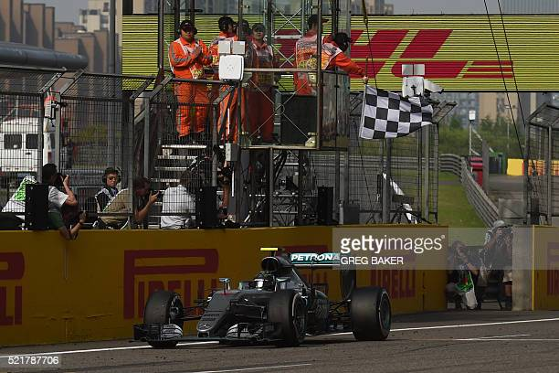 Mercedes AMG Petronas F1 Team's German driver Nico Rosberg crosses the finish line to win the Formula One Chinese Grand Prix in Shanghai on April 17,...