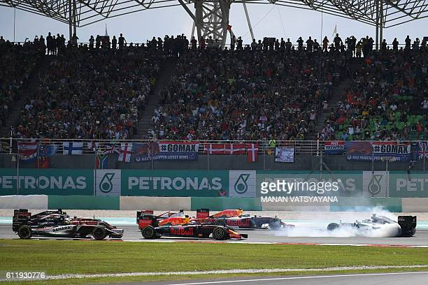 Mercedes AMG Petronas F1 Team's German driver Nico Rosberg faces the wrong direction, after spinning at the start of the Formula One Malaysian Grand...