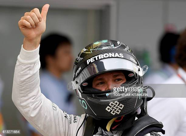 Mercedes AMG Petronas F1 Team's German driver Nico Rosberg gestures after taking pole position in the qualifying session at the Formula One Japanese...
