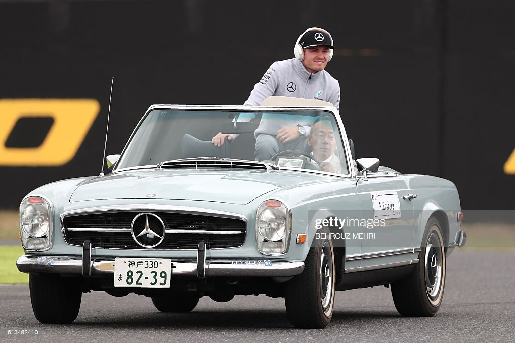 Mercedes AMG Petronas F1 Team's German driver Nico Rosberg rides in a classic Mercedes-Benz convertible during the drivers' parade for the Formula One Japanese Grand Prix in Suzuka on October 9, 2016. / AFP / BEHROUZ
