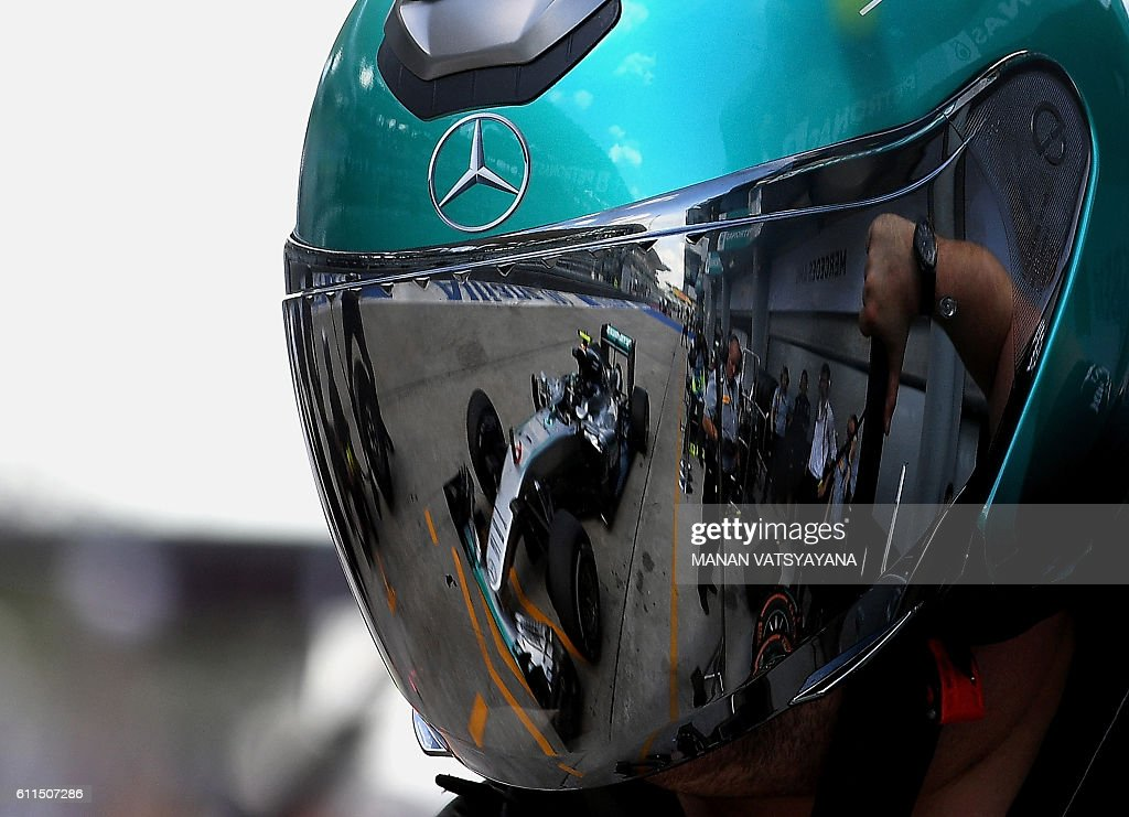 Mercedes AMG Petronas F1 Team's German driver Nico Rosberg's car is reflected in the helmet of a pit-crew member at the second practice session of the Formula One Malaysian Grand Prix in Sepang on September 30, 2016. / AFP / MANAN