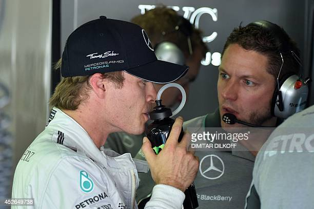 Mercedes AMG Petronas' German driver Nico Rosberg looks at a control screen in the pits during the first practice session at the Hungaroring circuit...