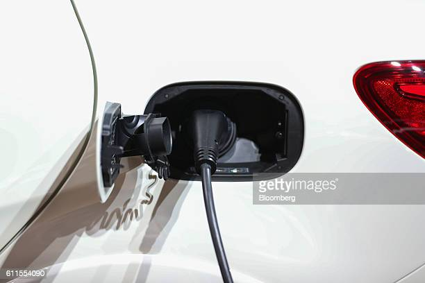 Mercedes B250e electric automobile, manufactured by Mercedes-Benz AG, sits connected to a charging plug during the second press day of the Paris...