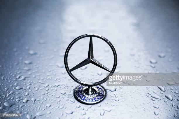 Mercedes Benz car emblem is covered with raindrops. Krakow, Poland on April 16, 2021