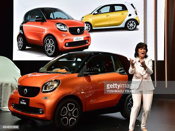 Mercedes Benz head of Smart Annette Winkler displays the new Smart Fortwo during a press preview at the Tokyo Motor Show in Tokyo on 28 2015 The...
