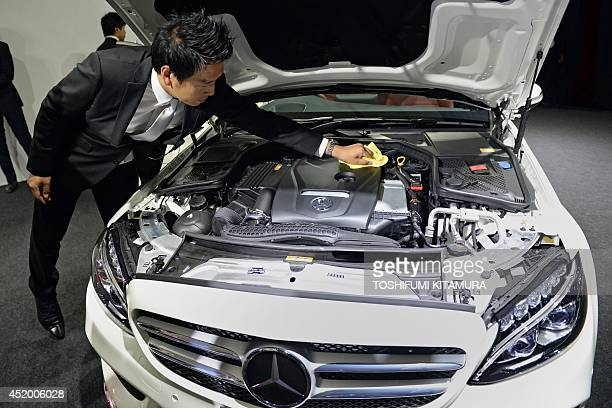 Mercedes Benz Japan employee cleans the engine of the company's new C-class sedan during its press preview in Tokyo on July 11, 2014. Mercedes Benz...