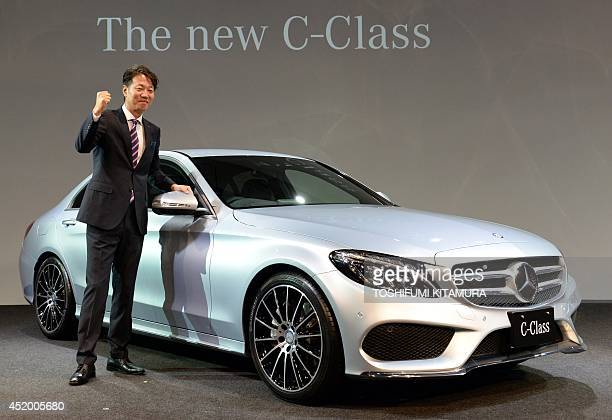 Mercedes Benz Japan president Kintaro Ueno poses beside the company's new C-class sedan during its press preview in Tokyo on July 11, 2014. Mercedes...