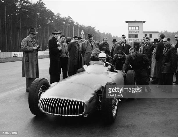 Mercedes Benz team manager Alfred Neubauer watches British driver Stirling Moss test drive a Mercedes W196 racing car during a trial run at...