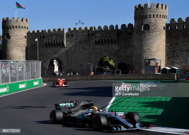 Mercedes' British driver Lewis Hamilton and Ferrari's German driver Sebastian Vettel steer their cars during the Formula One Azerbaijan Grand Prix at...