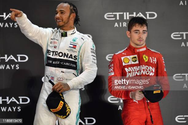 Mercedes' British driver Lewis Hamilton and Ferrari's Monegasque driver Charles Leclerc are pictured on the podium at the Yas Marina Circuit in Abu...