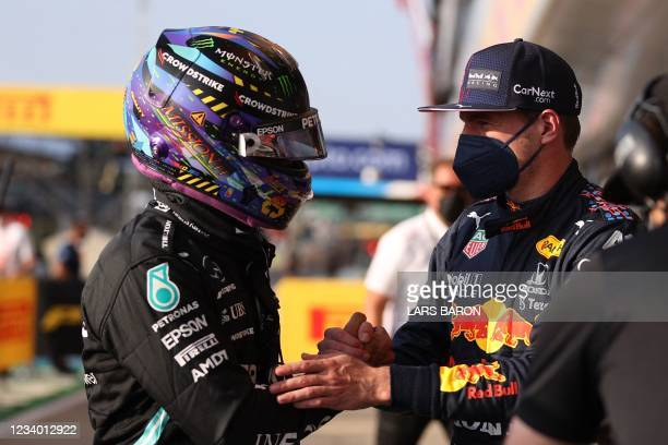 Mercedes' British driver Lewis Hamilton and Red Bull's Dutch driver Max Verstappen shake hands after the sprint qualifying session of the Formula One...