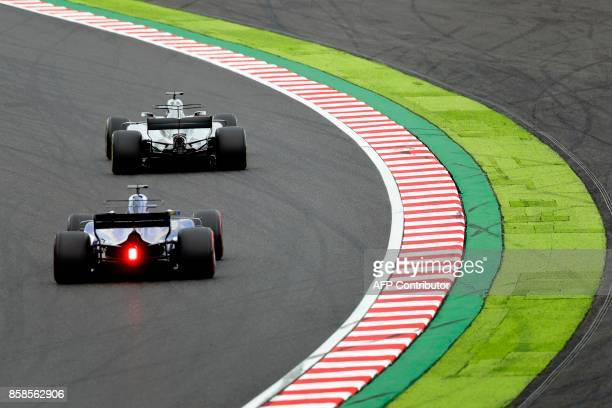 Mercedes' British driver Lewis Hamilton and Sauber's Swedish driver Marcus Ericsson drive during the qualifying session of the Formula One Japanese...