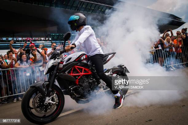 TOPSHOT Mercedes' British driver Lewis Hamilton arrives on a motorbike for a third practice session ahead of the Austrian Formula One Grand Prix in...