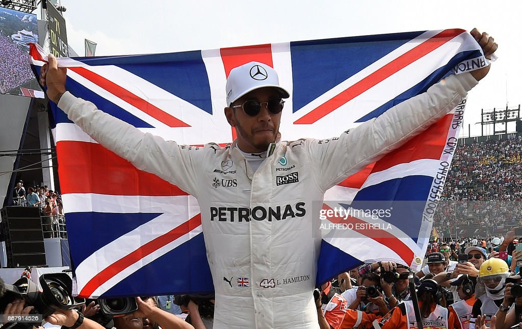 TOPSHOT - Mercedes' British driver Lewis Hamilton celebrates after winning his fourth Formula One world title despite finishing the Mexican Grand Prix in ninth place, at the Hermanos Rodriguez circuit in Mexico City on October 29, 2017. / AFP PHOTO / Alfredo ESTRELLA