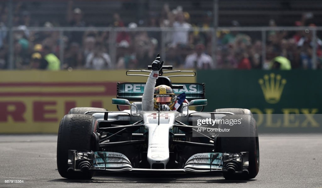 TOPSHOT - Mercedes' British driver Lewis Hamilton celebrates after winning his fourth Formula One world title despite finishing the Mexican Grand Prix in ninth place, at the Hermanos Rodriguez circuit in Mexico City on October 29, 2017. / AFP PHOTO / Yuri CORTEZ