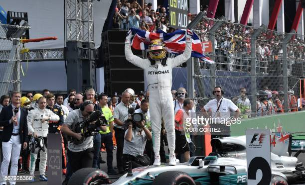 Mercedes' British driver Lewis Hamilton celebrates after winning his fourth Formula One world title despite finishing the Mexican Grand Prix in ninth...