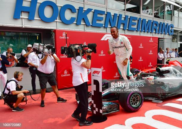 TOPSHOT Mercedes' British driver Lewis Hamilton celebrates after winning the German Formula One Grand Prix at the Hockenheim racing circuit on July...