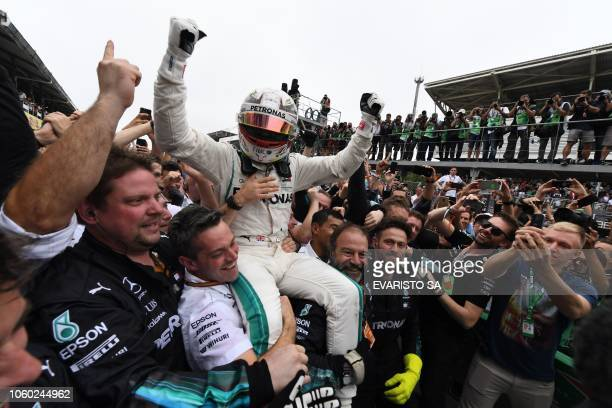 TOPSHOT Mercedes' British driver Lewis Hamilton celebrates after winning the F1 Brazil Grand Prix while Mercedes took the constructors title at the...