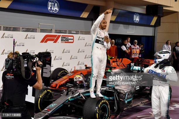 TOPSHOT Mercedes' British driver Lewis Hamilton celebrates after winning the Formula One Bahrain Grand Prix at the Sakhir circuit in the desert south...