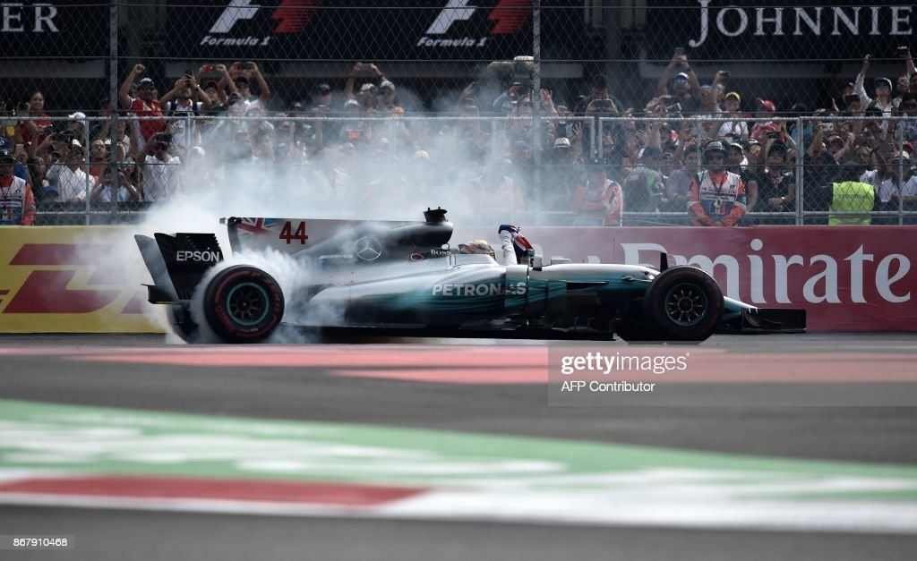 TOPSHOT - Mercedes' British driver Lewis Hamilton celebrates before the crowd after winning his fourth Formula One world title despite finishing the Mexican Grand Prix in ninth place, at the Hermanos Rodriguez circuit in Mexico City on October 29, 2017. / AFP PHOTO / Yuri CORTEZ