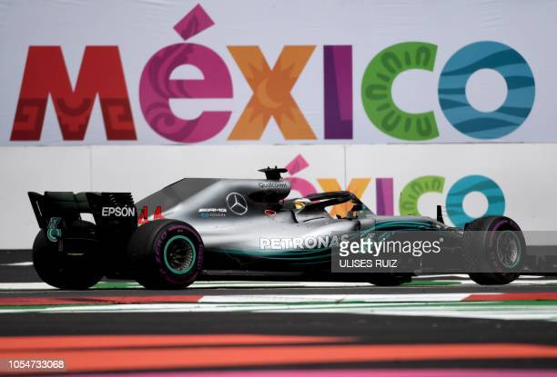 Mercedes' British driver Lewis Hamilton celebrates his fifth drivers' title after the F1 Mexico Grand Prix at the Hermanos Rodriguez circuit in...