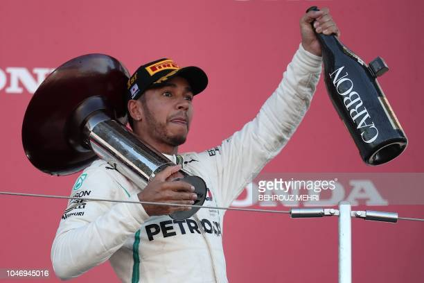 TOPSHOT Mercedes' British driver Lewis Hamilton celebrates on the podium after his victory in the Formula One Japanese Grand Prix at Suzuka on...