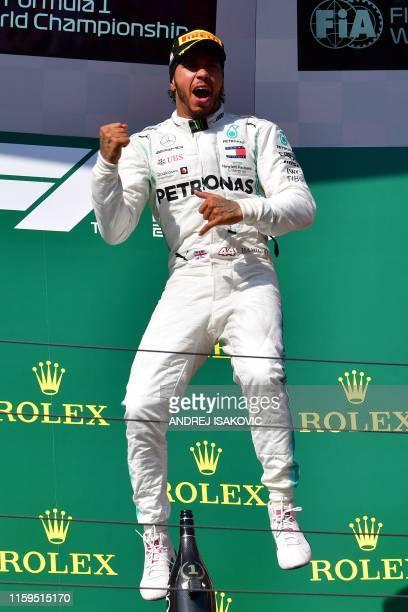 Mercedes' British driver Lewis Hamilton celebrates on the podium after the Formula One Hungarian Grand Prix at the Hungaroring circuit in Mogyorod...