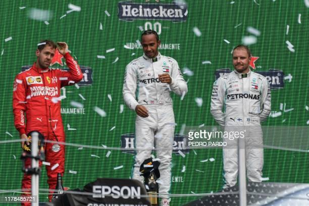 Mercedes' British driver Lewis Hamilton celebrates on the podium after winning the F1 Mexico Grand Prix next to runnerup Ferrari's Sebastian Vettel...