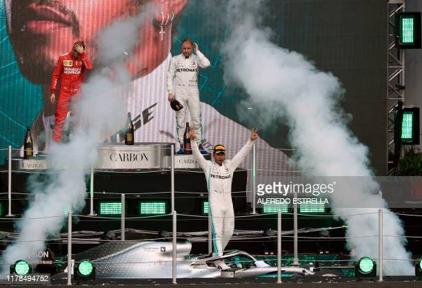 Mercedes' British driver Lewis Hamilton celebrates on the podium after winning the F1 Mexico Grand Prix next to runnerup Ferrari's Sebastian Vettel...