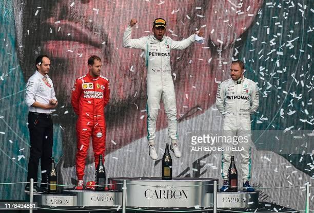 Mercedes' British driver Lewis Hamilton celebrates on the podium after winning the F1 Mexico Grand Prix, next to runner-up Ferrari's Sebastian Vettel...