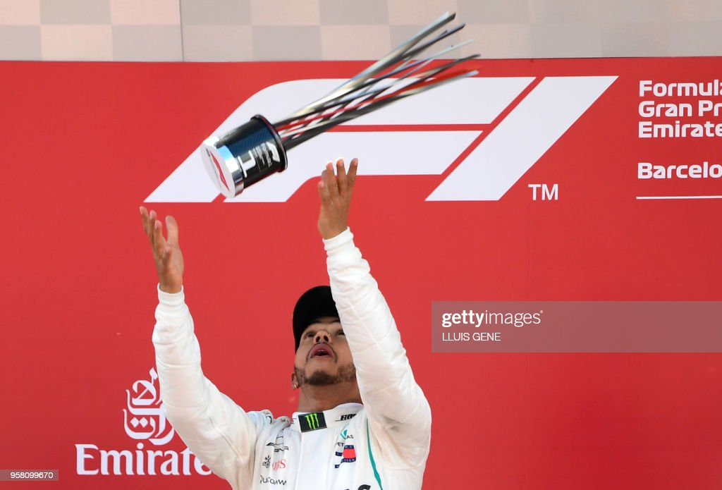 TOPSHOT - Mercedes' British driver Lewis Hamilton celebrates on the podium after winning the Spanish Formula One Grand Prix at the Circuit de Catalunya in Montmelo in the outskirts of Barcelona on May 13, 2018.