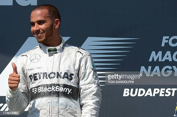 Mercedes' British driver Lewis Hamilton celebrates on the podium at the Hungaroring circuit in Budapest on July 28 2013 after the Hungarian Formula...