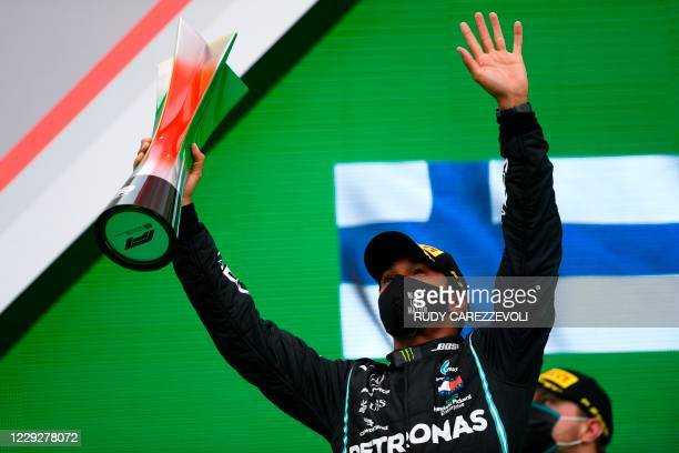 Mercedes' British driver Lewis Hamilton celebrates on the podium with the trophy after winning the Portuguese Formula One Grand Prix at the Autodromo...