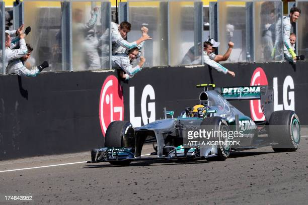 Mercedes' British driver Lewis Hamilton celebrates winning as he passes teammates at the Hungaroring circuit in Budapest on July 28, 2013 after the...
