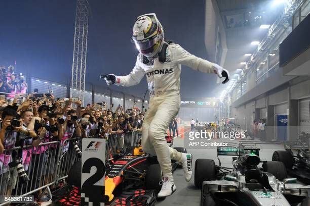 TOPSHOT Mercedes' British driver Lewis Hamilton celebrates winning the Formula One Singapore Grand Prix in Singapore on September 17 2017 / AFP PHOTO...