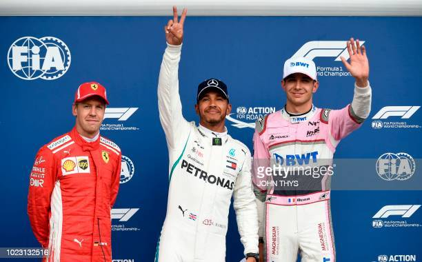 Mercedes' British driver Lewis Hamilton celebrates winning the pole position next to second placed Ferrari's German driver Sebastian Vettel and third...