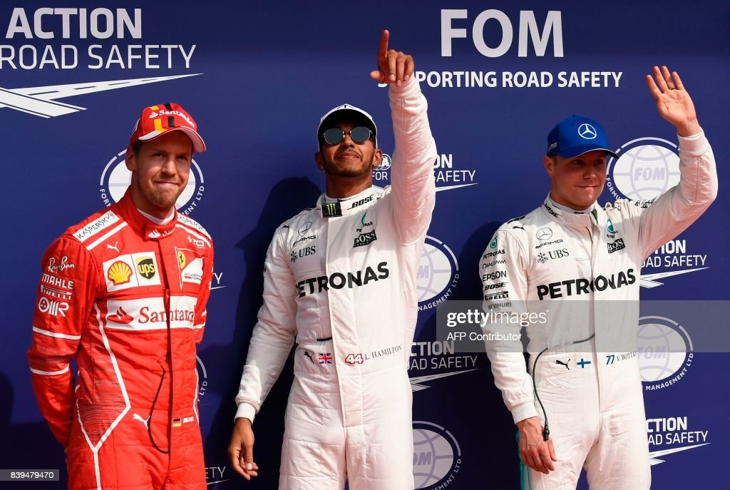 TOPSHOT - Mercedes' British driver Lewis Hamilton (C) celebrates winning the pole position next to second placed Ferrari's German driver Sebastian Vettel (L) and third placed Mercedes' Finnish driver Valtteri Bottas after the qualifying session at the Spa-Francorchamps circuit in Spa on August 26, 2017 ahead of the Belgian Formula One Grand Prix. /