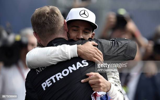 Mercedes' British driver Lewis Hamilton celebrates with a teammate after winning his fourth Formula One world title despite finishing the Mexican...