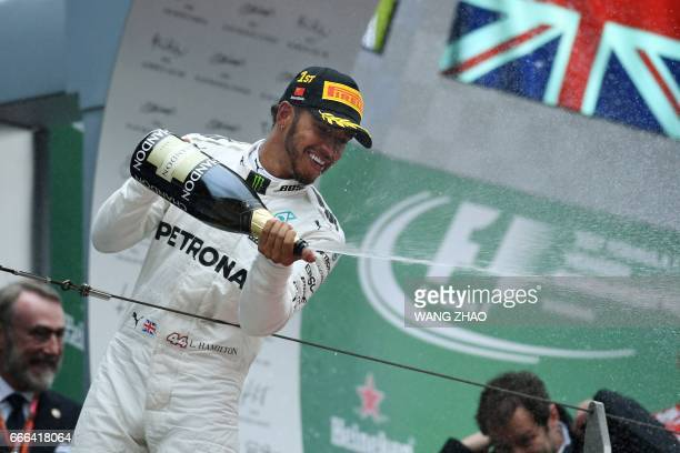 Mercedes' British driver Lewis Hamilton celebrates with champagne on the podium after winning the Formula One Chinese Grand Prix in Shanghai on April...