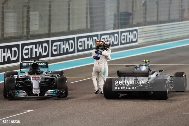 TOPSHOT Mercedes' British driver Lewis Hamilton celebrates with his teammate Finnish driver Valtteri Bottas at the end of the Abu Dhabi Formula One...