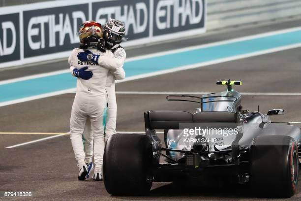 Mercedes' British driver Lewis Hamilton celebrates with his teammate Finnish driver Valtteri Bottas at the end of the Abu Dhabi Formula One Grand...