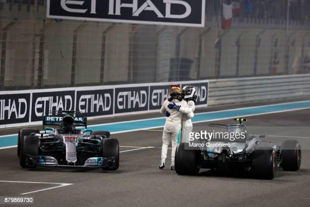 Mercedes' British driver Lewis Hamilton celebrates with his teammate Finnish driver Valtteri Bottas at the end of the Abu Dhabi Formula One Grand Prix