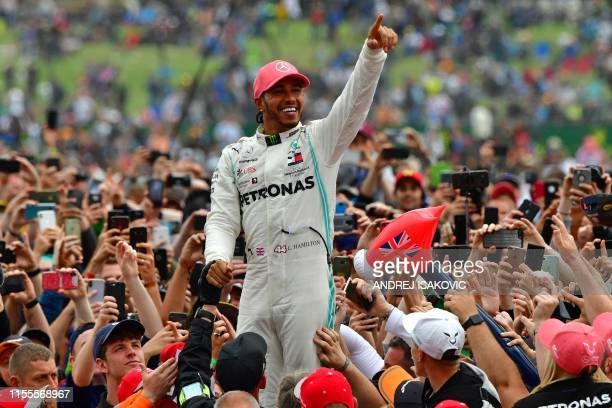 Mercedes' British driver Lewis Hamilton celebrates with supporters after victory in the British Formula One Grand Prix at the Silverstone motor...