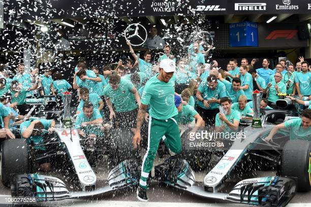 TOPSHOT Mercedes' British driver Lewis Hamilton celebrates with the Mercedes team after winning the F1 Brazil Grand Prix and taking the constructors...