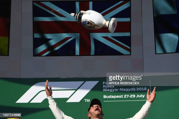 TOPSHOT Mercedes' British driver Lewis Hamilton celebrates with the trophy on the podium after winning the Formula One Hungarian Grand Prix at the...